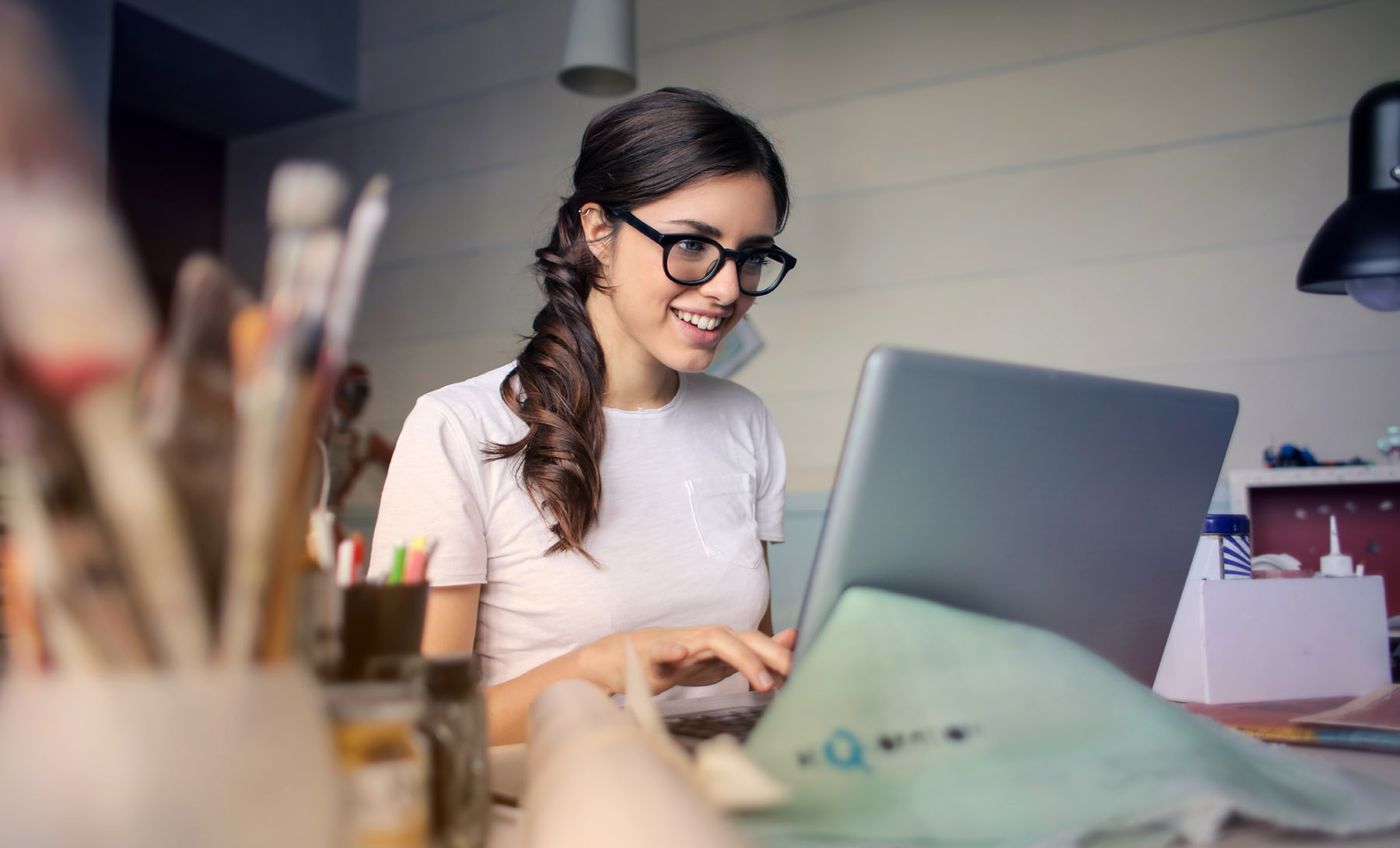 Woman in art studio working on laptop and smiling