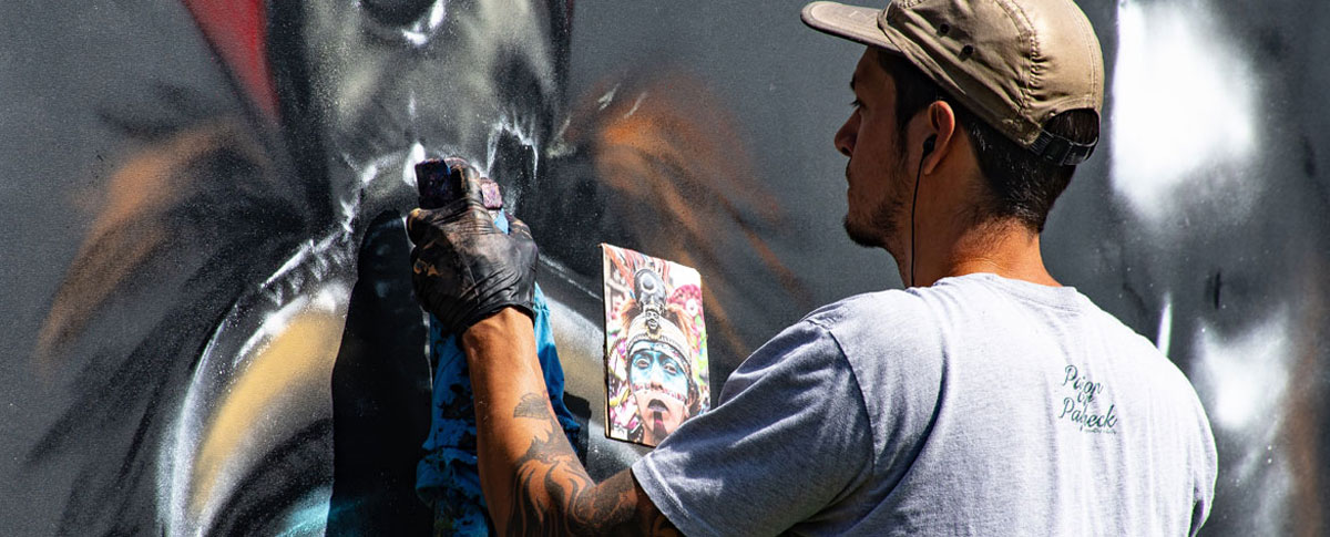 Man painting mural on wall