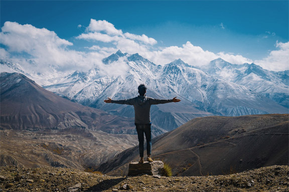 Man overlooking mountain range with arms wide open in gratitude and courage